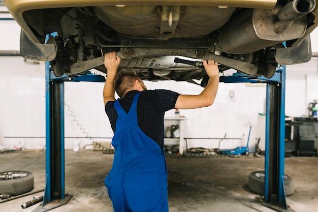 自動車の底を調べる修理士