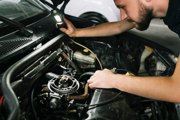 Техник, проверяющий двигатель автомобиля