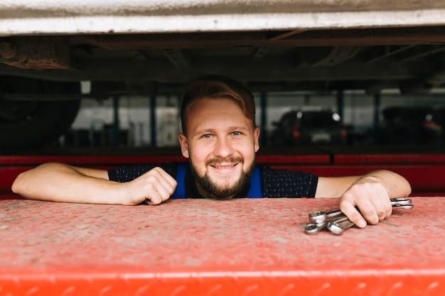 車のワークショップでハンサムな修理士
