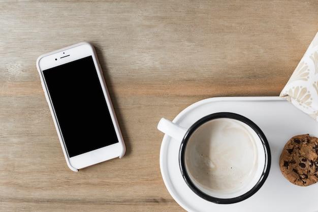 白いトレイと木製の背景にスマートフォンにクッキーとコーヒーカップ