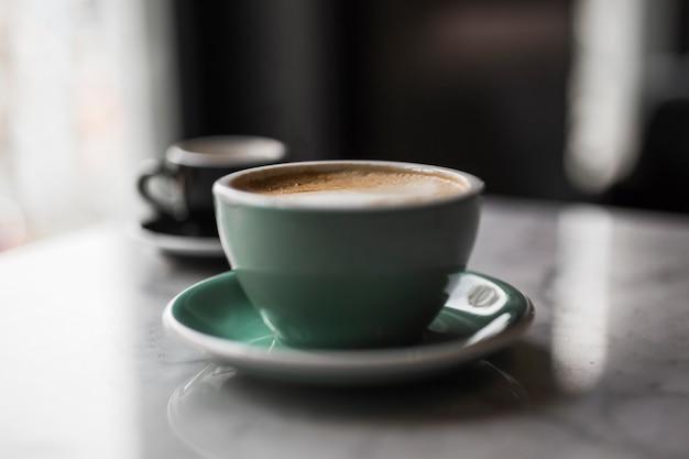 テーブル上のカプチーノとソーサーのセラミックカップ