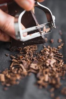 ピーラーでチョコレートバーをシェービングする人の手のクローズアップ