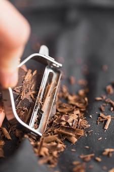 ピーラーでチョコレートバーをシェービングする人の手のマクロショット