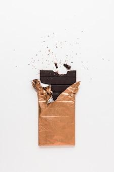 白い背景に一口の欠けた黄金の箔で包まれたダークチョコレートバー