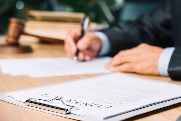 法廷で木製の机の上に契約書を貼ったクリップボード