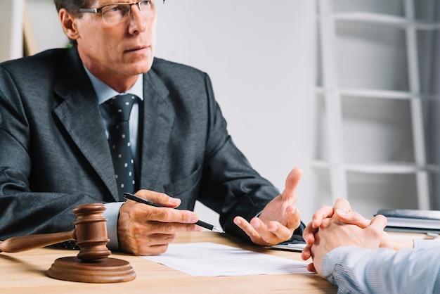 彼の顧客に法的状況を説明する弁護士