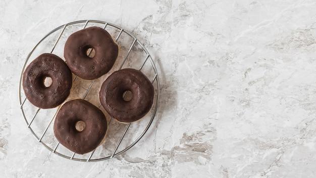 大理石のテクスチャ付きの背景の上に金属製のラックにチョコレートドーナツ
