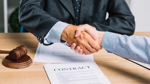 男性の弁護士は、契約用紙上のクライアントとの握手をテーブルに