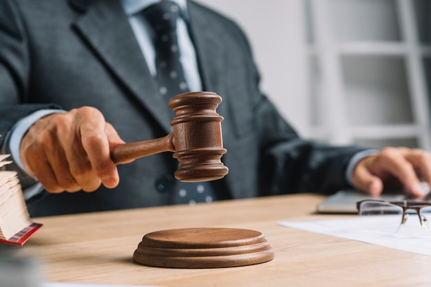 Мужской судья-адвокат, дающий вердикт, ударяя молотком молотком по зондирующему блоку