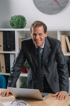 法廷で木製テーブルにノートパソコンを持つ熟した男性の弁護士を笑顔にする