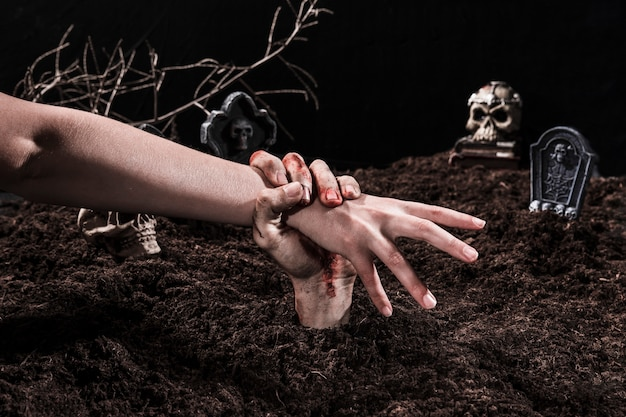 ハロウィン墓地でゾンビの手を引く人