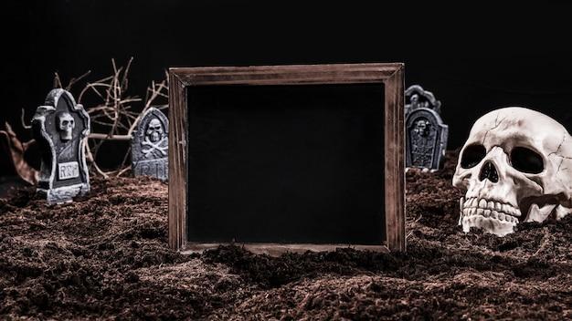 Черный пустой знак, стоящий на кладбище с черепом