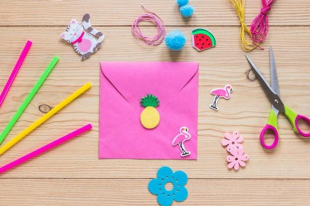 ピンクの封筒は、木製のテクスチャの背景にステッカーで飾られて
