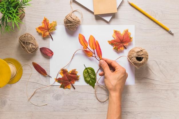 木製のテクスチャの背景の上に白い紙の弦スプールで偽の葉を結んでいる人