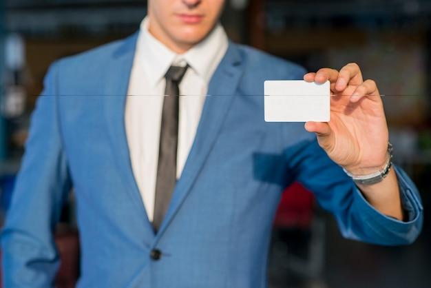 空の訪問カードを表示しているビジネスマンの手のクローズアップ