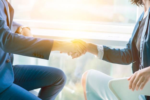 Солнечный свет падает на двух бизнесменов, рукопожатие