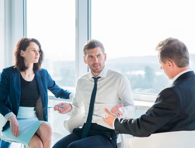 オフィスでの会話を持つビジネスマンのグループ