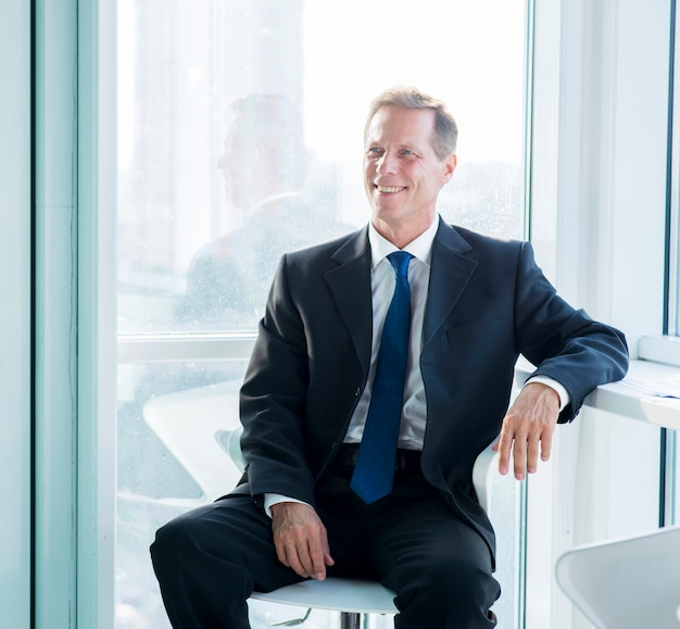 オフィスで椅子に座っている笑顔の成熟したビジネスマン