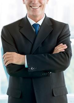 折りたたみ式の腕を持つ笑顔のビジネスマンのクローズアップ
