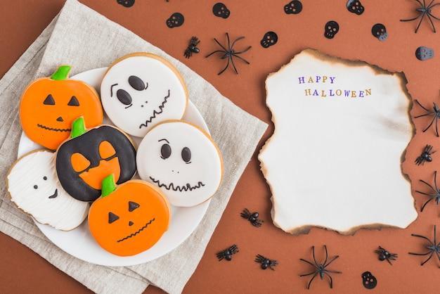 Хэллоуинские пряники на тарелке возле горящего листа
