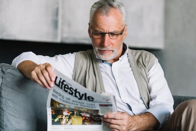 新聞を読んでいるソファに座っている老人の肖像
