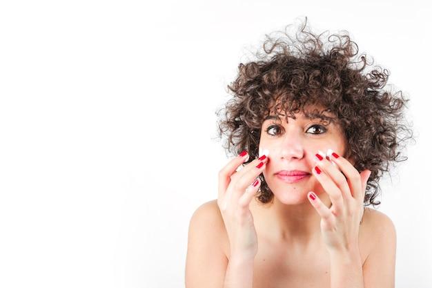 Молодая женщина, применение косметический крем на ее лице на белом фоне
