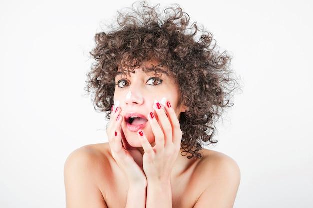 Красота молодая женщина с открытым ртом, применяя крем на лице