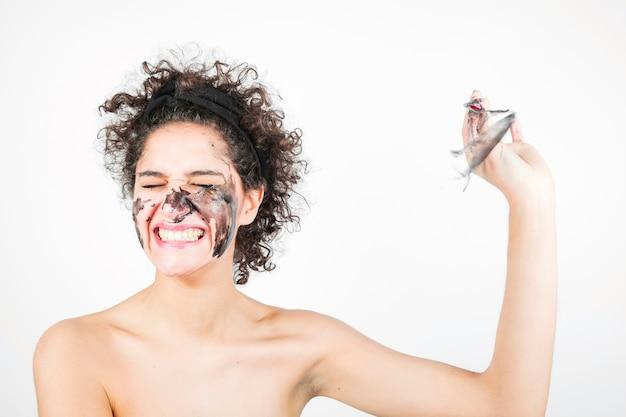 白い背景に顔のマスクを削除する笑顔の幸せな若い女性