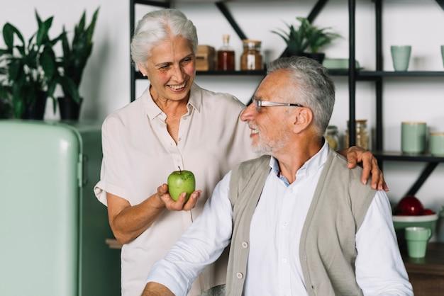 キッチンに立っている彼女の夫に緑のリンゴを示す笑顔の女性