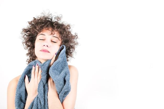 白い背景にタオルで自分自身を拭く女性