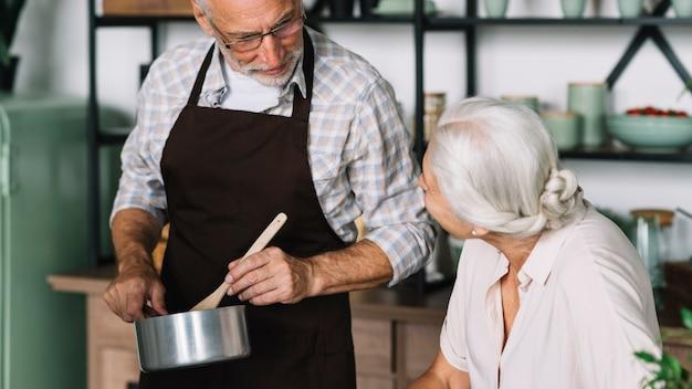 Старший женщина, глядя на человека, приготовления пищи на кухне
