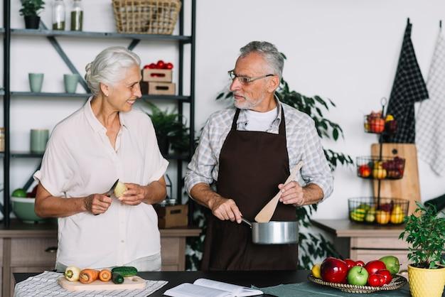 お互いを見て台所で食べ物を準備しているシニアカップルのクローズアップ
