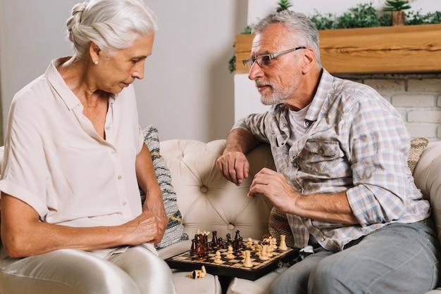 チェスをするソファーに座っているシニアカップル