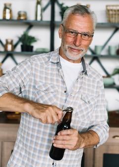 Портрет старшего человека, открывая бутылку пива с открывалкой