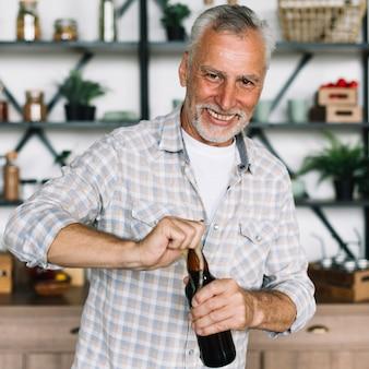 Портрет пожилого человека, открывающего бутылку пива