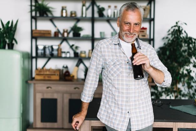 Улыбаясь старший человек, пить пиво из бутылки дома