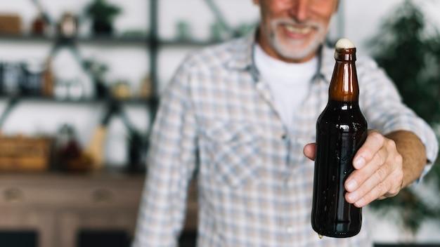 Крупный план старшего человека, предлагающего бутылку пива