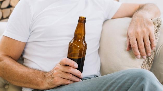 Крупным планом человек, держащий бутылку пива