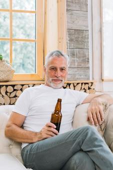 Портрет старшего человека, сидящего на диване, глядя на камеру, проведение бутылку пива