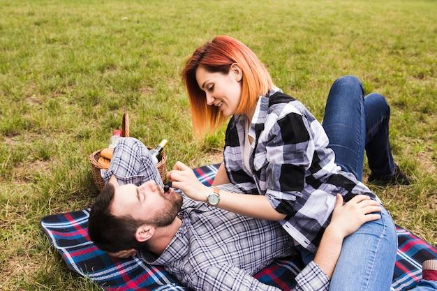 緑の草の上に毛布に横たわっている彼女のボーイフレンドにチェリーを与えている若い女性に笑顔