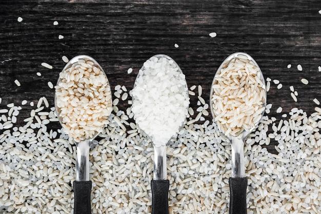 Верхний вид сырого риса в ложке на черном фоне