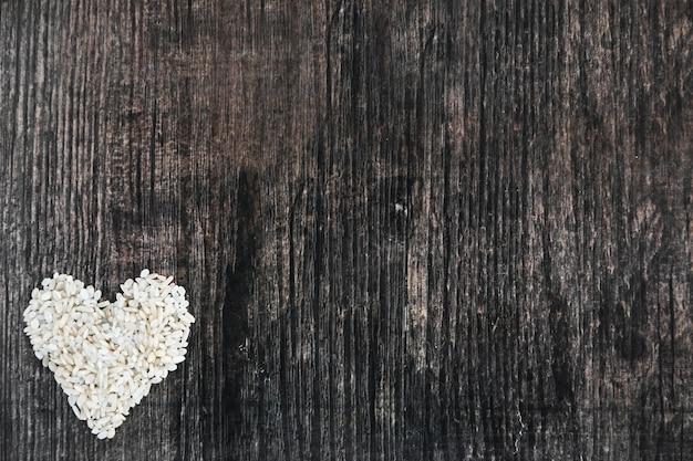 木製の黒い背景で作られた米の心臓の形