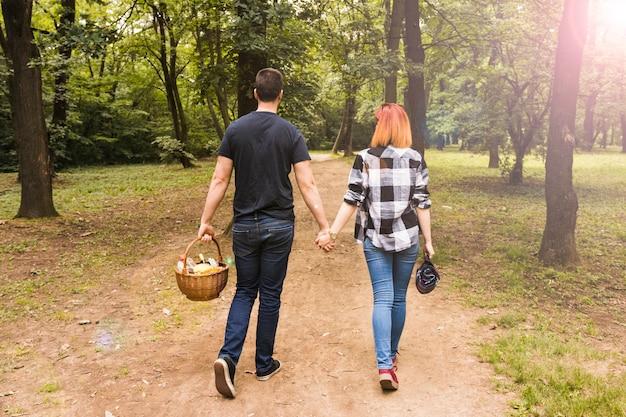 公園でのダートロードを歩くピクニックバスケットを持っているカップルのリアビュー