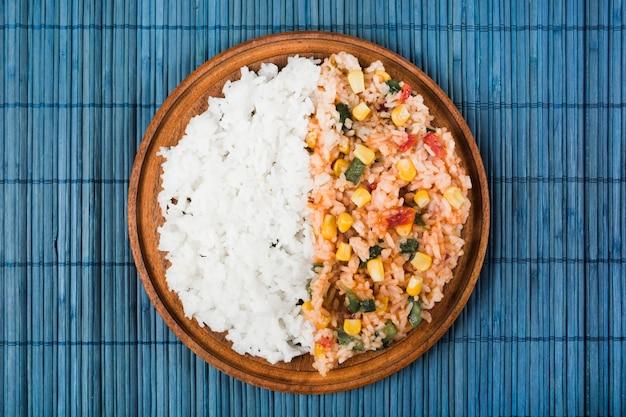 青い食卓の上の木製のプレート上の中国の炒めと蒸し米
