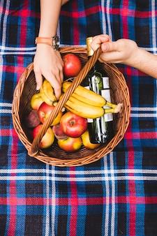 フルーツとシャンパンのボトルのピクニックバスケットにカップルの手
