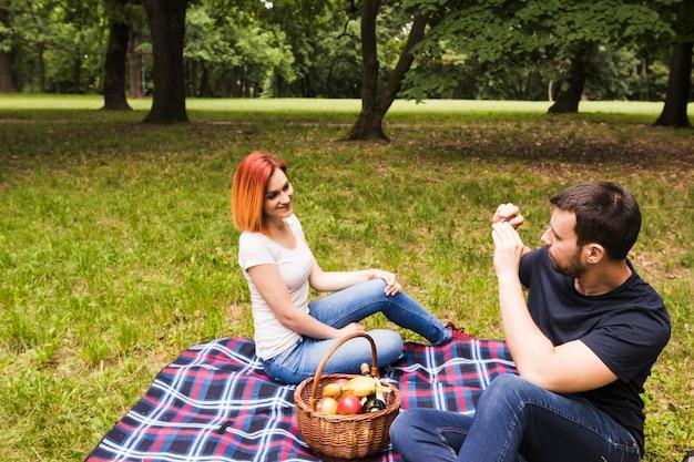 ピクニックで携帯電話で彼女のガールフレンドの写真を撮っている男