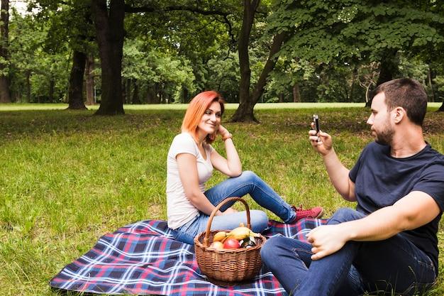 ピクニックでスマホの彼女の笑顔のガールフレンドの写真を撮っている男