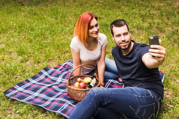 ピクニックで携帯電話で彼女の笑顔のガールフレンドとセルフを取る男