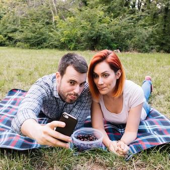 屋外のピクニックで携帯電話でセルフを取る若いカップル