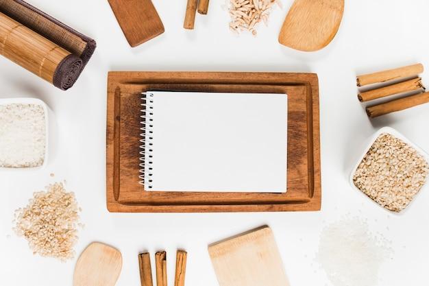 米とシナモンスティックで囲まれた木製トレイにスパイラルのメモ帳